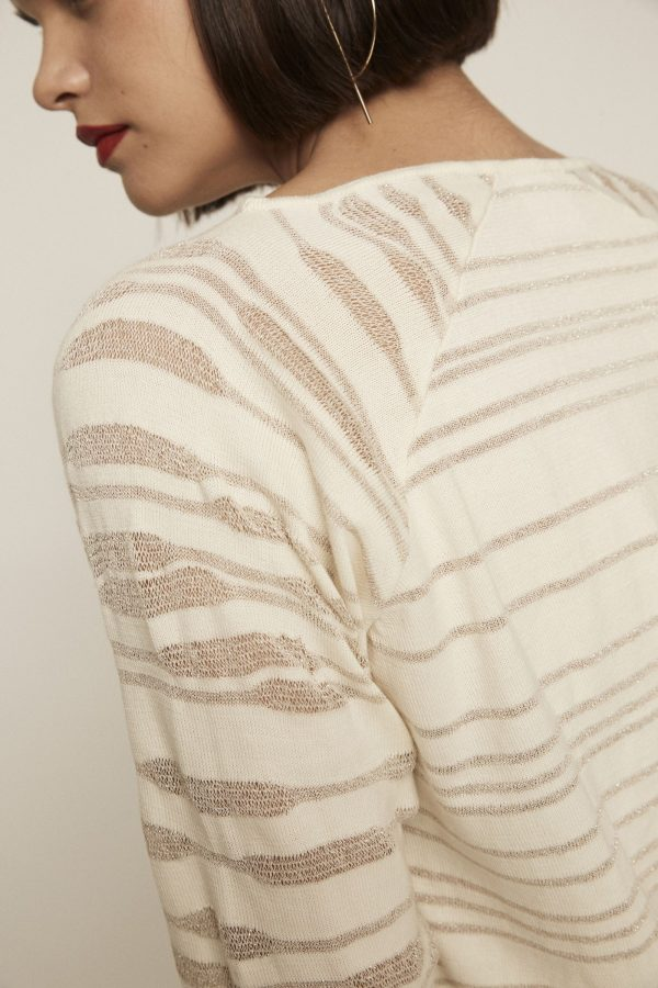 Off-white knit sweater with boat neckline, see-through motifs and elastic cuffs.